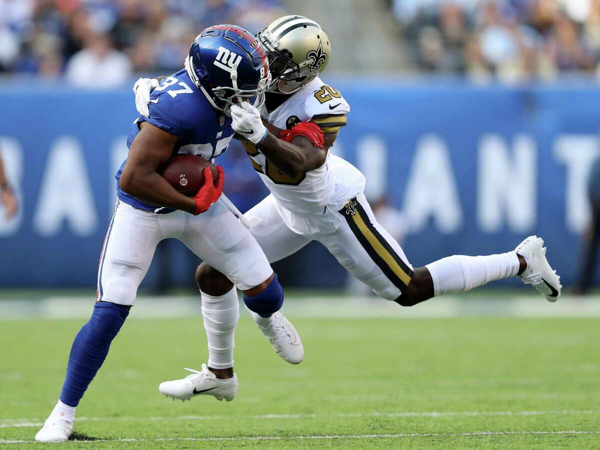 EAST RUTHERFORD, NJ - SEPTEMBER 30: Ken Crawley #20 of the New Orleans Saints grabs the facemask of Sterling Shepard #87 of the New York Giants as he makes the tackle on September 30,2018 at MetLife Stadium in East Rutherford, New Jersey. (Photo by Elsa/Getty Images)