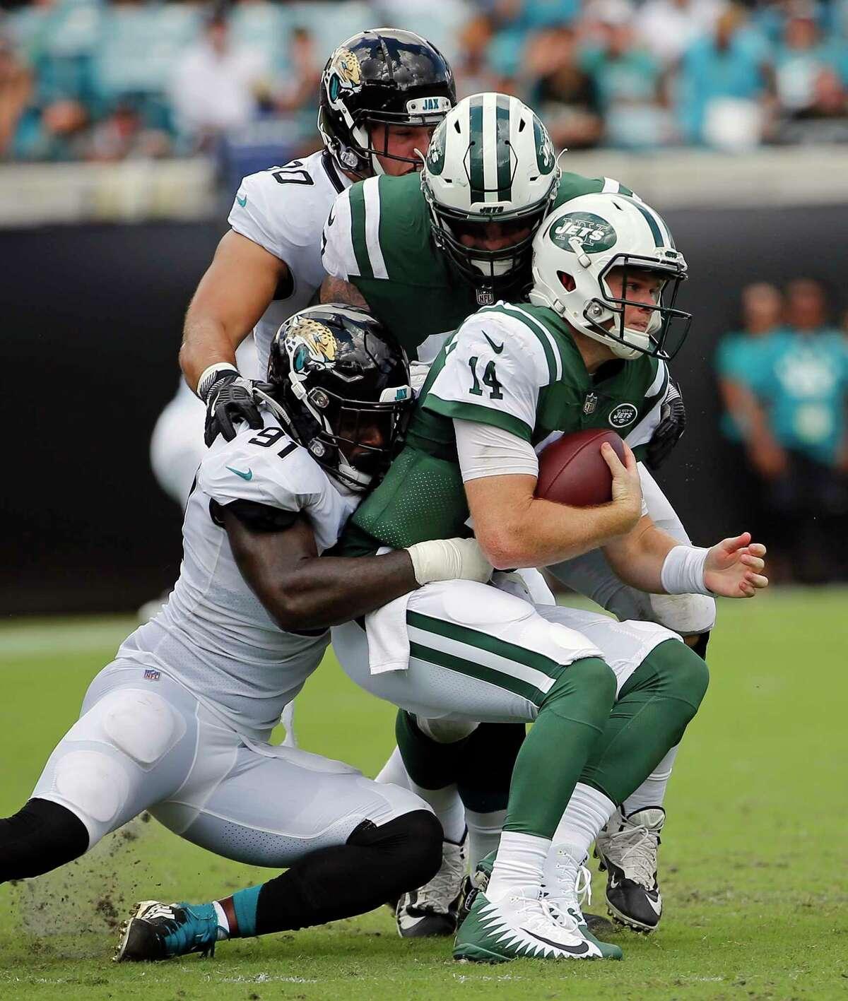 Jacksonville Jaguars defensive end Yannick Ngakoue, lower left, sacks New York Jets quarterback Sam Darnold (14) during the first half of an NFL football game, Sunday, Sept. 30, 2018, in Jacksonville, Fla. (AP Photo/Stephen B. Morton)