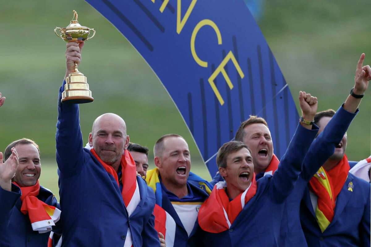Europe team captain Thomas Bjorn holds up the cup as he celebrates with his players after the European team won the 2018 Ryder Cup golf tournament at Le Golf National in Saint Quentin-en-Yvelines, outside Paris, France, Sunday, Sept. 30, 2018. (AP Photo/Alastair Grant)