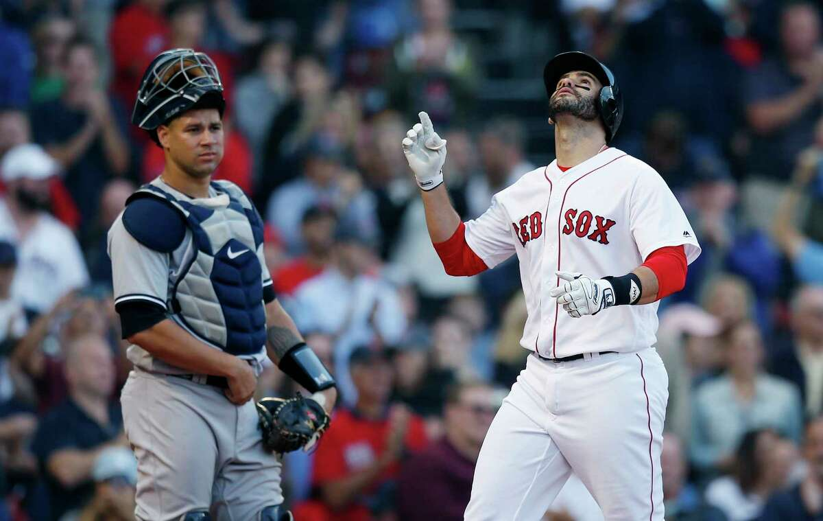 New York Yankees' Gary Sanchez, left, watches as Boston Red Sox's J.D. Martinez celebrates his three-run home run during the fourth inning of a baseball game in Boston, Sunday, Sept. 30, 2018. (AP Photo/Michael Dwyer)