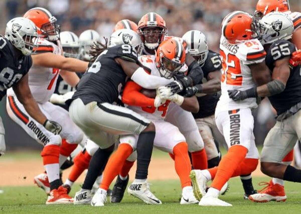 Oakland Raiders' Fadol Brown wraps up Cleveland Browns' Carlos Hyde in 3rd quarter of Raiders' 45-42 overtime win during NFL game at Oakland Coliseum in Oakland, Calif. on Sunday, September 30, 2018.