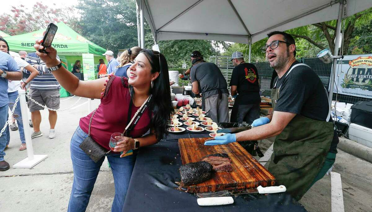 Chef Aaron Franklin (right) poses for a photo with Corina Villalobes as he sliced brisket at the 2018 Southern Smoke festival.