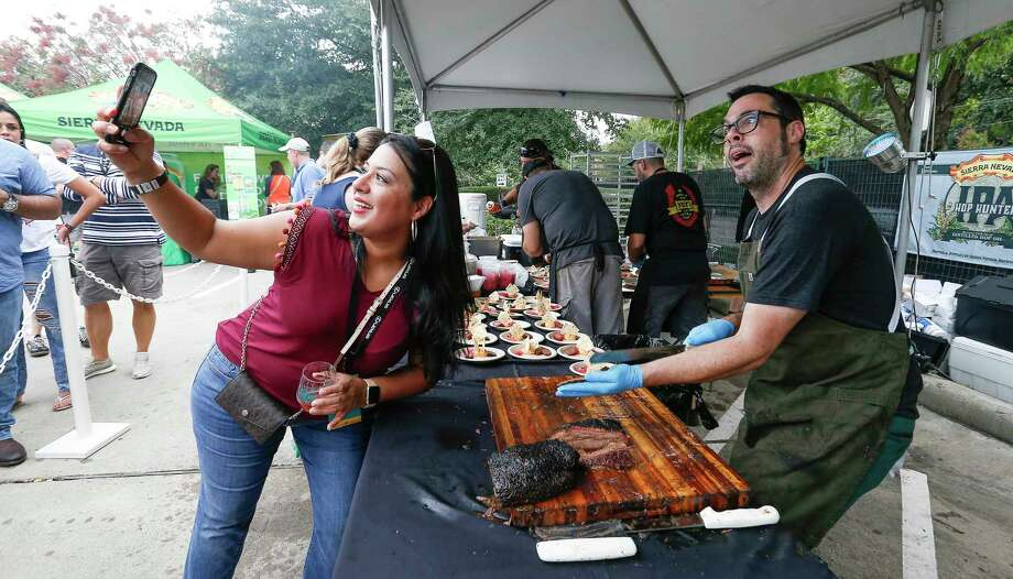 Chef Aaron Franklin (right) poses for a photo with Corina Villalobes as he sliced brisket at the 2018 Southern Smoke festival. Photo: Steve Gonzales, Staff Photographer / © 2018 Houston Chronicle