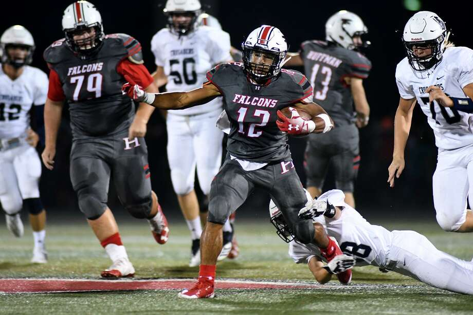 Huffman-Hargrave junior running back A.J. San Miguel (12) tries to break the grasp of , Concordia Lutheran junior defensive back Patton Baxterduring the 2nd quarter of their matchup at Falcon Stadium in Huffman on Sept. 28, 2018. Photo: Jerry Baker, Houston Chronicle / Contributor / Houston Chronicle