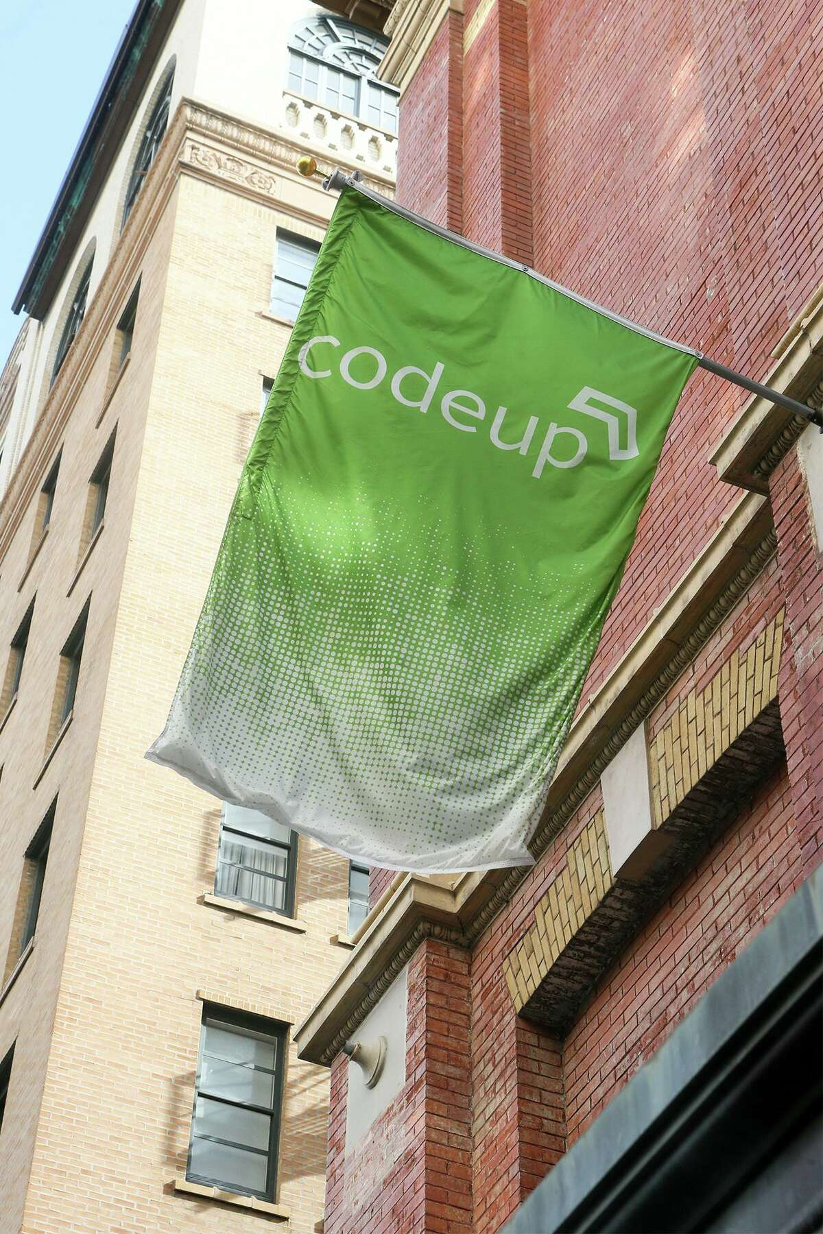 A Copeup sign flying outside the street entrance to Codeup, a company downtown that offers coding bootcamps for aspiring software developers at 600 Navarro St. #350 on Tuesday, Sept. 25, 2018.