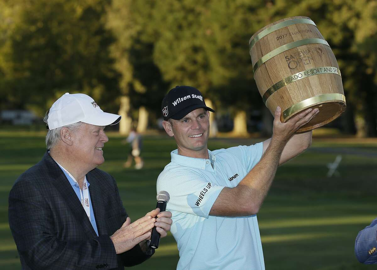 Brendan Steele (right) holds up his trophy on the 18th green at Silverado Resort after winning the Safeway Open in October 2017. Hall of Famer Johnny Miller (left) looks on.