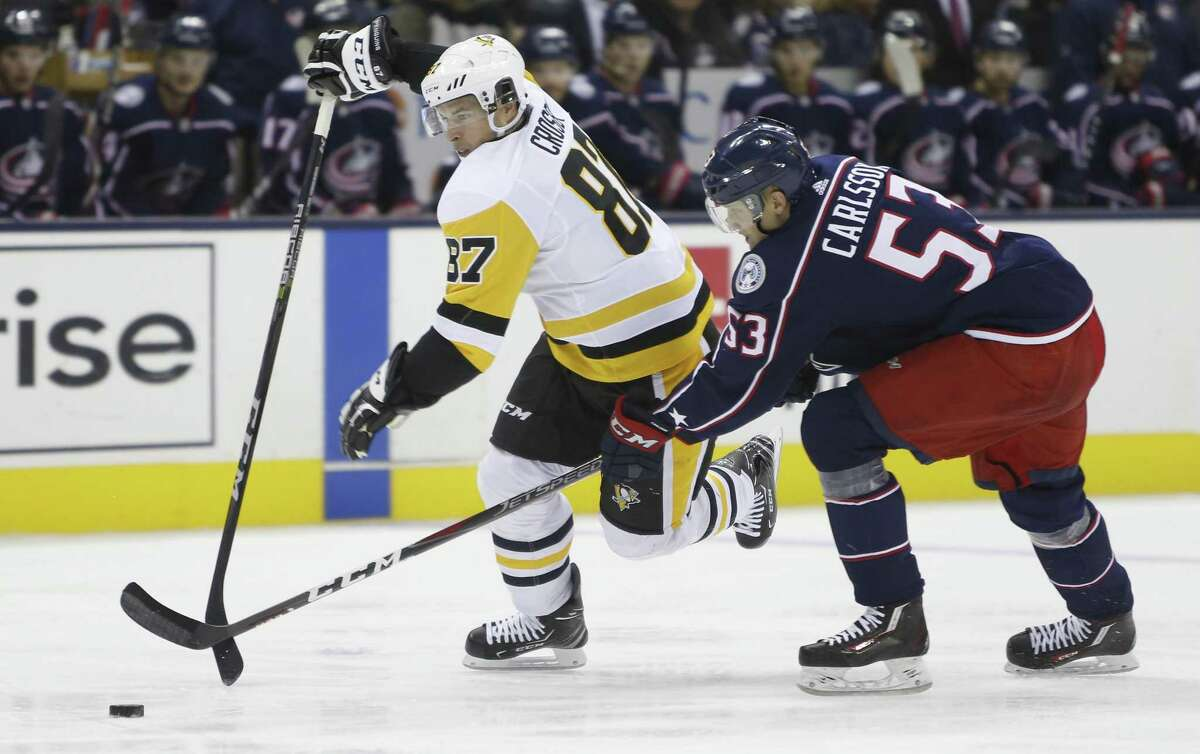 In this Sept. 28, 2018, file photo Pittsburgh Penguins' Sidney Crosby, left, tries to skate past Columbus Blue Jackets' Gabriel Carlsson during the third period of a preseason NHL hockey game in Columbus, Ohio.