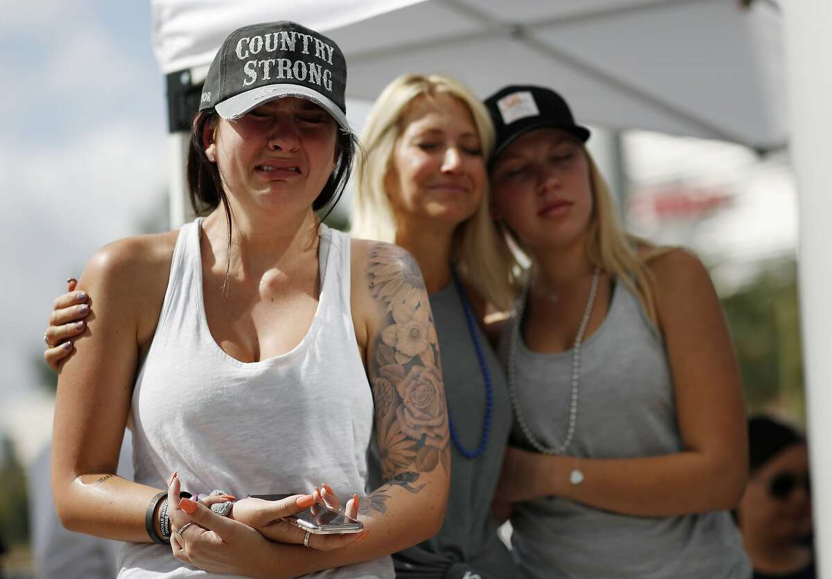 From left, Michaela Stilwell, Melinda Stilwell and Taylor Curtis attend a prayer service on the anniversary of the Oct.1, 2017 mass shooting, Monday, Oct. 1, 2018, in Las Vegas. Michaela Stilwell and Taylor Curtis attended the country music festival last year and came back to Las Vegas for the anniversary. (AP Photo/John Locher)