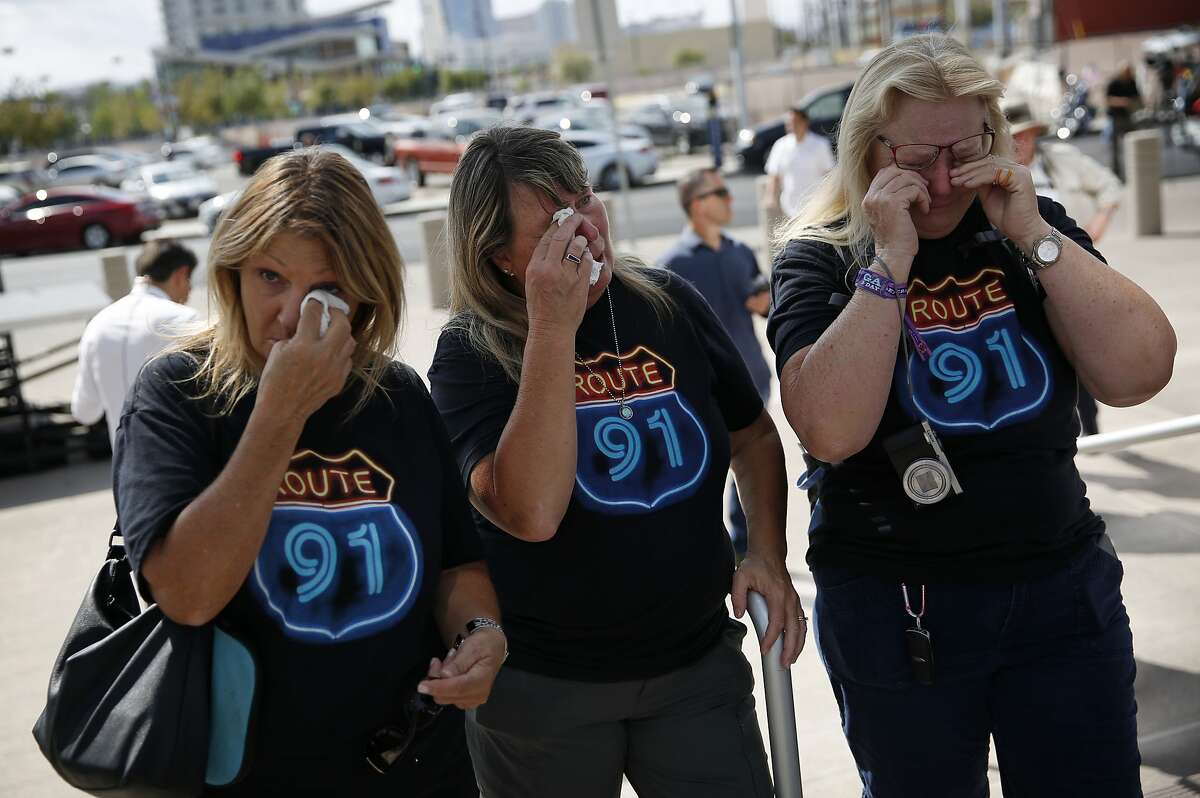 """From left, Linda Hazelwood, Michelle Hamel and Jann Blake, all from California, cry as they attend a prayer service on the anniversary of the Oct. 1, 2017 mass shooting, Monday, Oct. 1, 2018, in Las Vegas. The three saw bullets hit the ground near them when they attended the country music festival last year, and housed other attendees in their hotel room that night. """"We needed this closure,"""" said Jann Blake, """"It's been a heavy year."""" (AP Photo/John Locher)"""