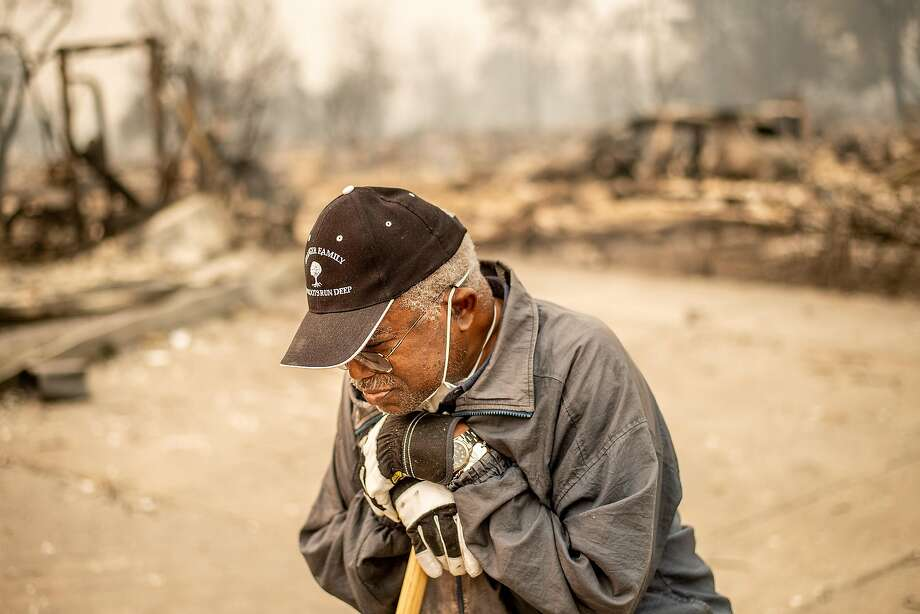 Henry Granger pauses while searching through the remains of his family's Coffey Park home after the Tubbs Fire. Photo: Noah Berger / Special To The Chronicle 2017