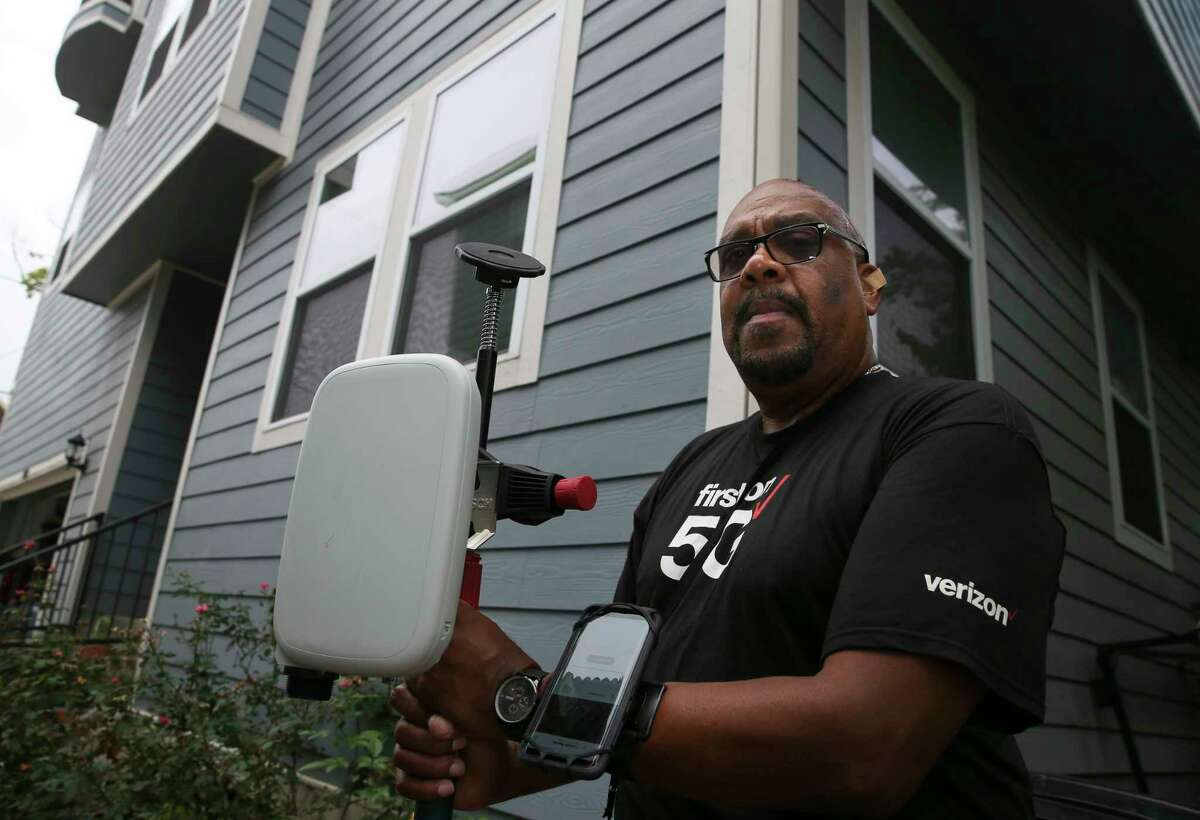 Verizon contractor Darryl McQueen, of Asurion, poses for a photograph before he goes to test the 5G broadband signals at Clayton and Emily Harris' house in the Heights with an antenna on Monday, Oct. 1, 2018, in Houston. The Harrises were the first Verizon 5G broadband customers in the nation.