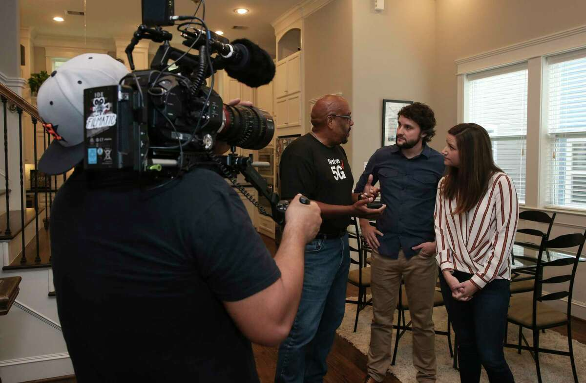 Verizon contractor Darryl McQueen, of Asurion, explains the 5G broadband set up process to Clayton and Emily Harris' house in the Heights while two video crew are filming on Monday, Oct. 1, 2018, in Houston. The Harrises were the first Verizon 5G broadband customers in the nation.