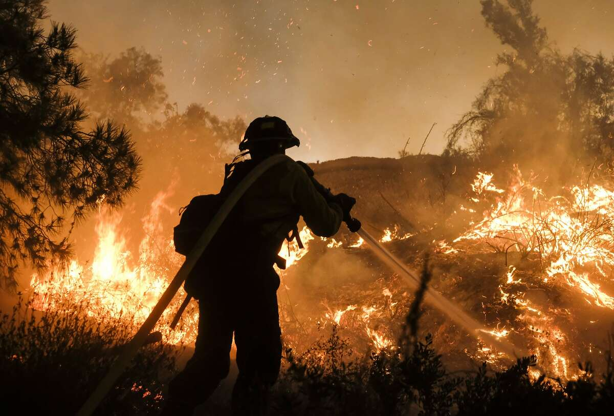 FILE - In this Aug. 9, 2018, file photo, a firefighter battles the Holy Fire burning in the Cleveland National Forest along a hillside at Temescal Valley in Corona, Calif. California is in the midst of another devastating year of wildfires and finding the causes for the worst of them can be critical to identifying better fire-prevention techniques. But often investigators can't figure out a cause. (AP Photo/Ringo H.W. Chiu, File)