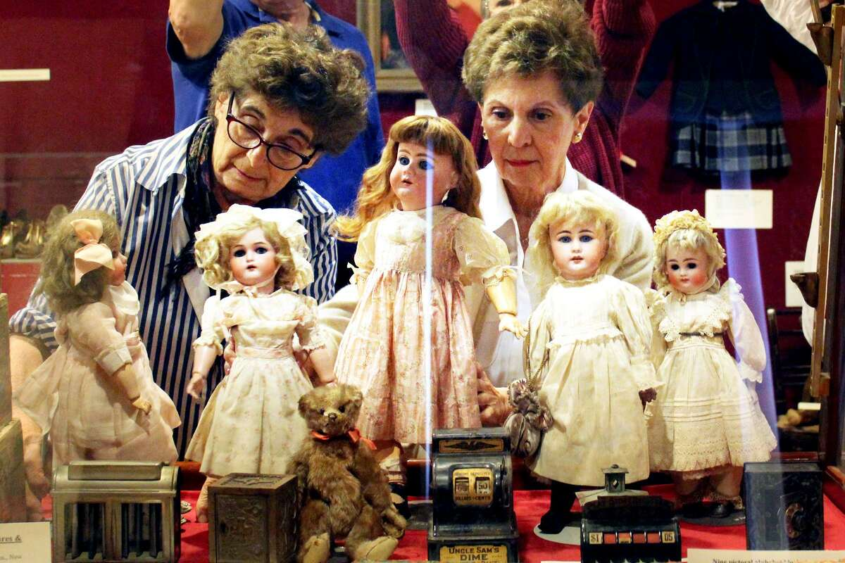 Helen Devin and Rosemarie Vacca place dolls in a display for the Stamford History Center's new exhibition,