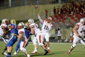 Eric Rodriguez (11) of Travis releases a touchdown pass to Parker Washington (3) in the second quarter of a high school football game between the Elkins Knights and the Travis Tigers on Thursday, Sept. 27, at Hall Stadium in Missouri City.