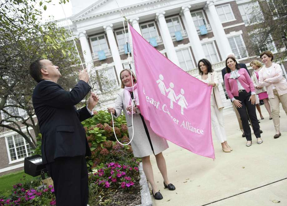 First Selectman Peter Tesei and Greenwich Hospital Breast Cancer Center Medical Director Dr. Barbara Ward raise a pink BCA flag during the Breast Cancer Alliance's GoForPink Flag Raising at Town Hall in Greenwich, Conn. Monday, Oct. 1, 2018. The Town of Greenwich and many local merchants partnered together for a series of events promoting Breast Cancer Awareness Month including an educational forum, and shopping and dining days to raise funds for BCA. BCA President Mary Jeffery, BCA Executive Director Yonni Wattenmaker, Greenwich Hospital Breast Cancer Center Medical Director Dr. Barbara Ward, and First Selectman Peter Tesei spoke at the flag raising. Photo: Tyler Sizemore / Hearst Connecticut Media / Greenwich Time