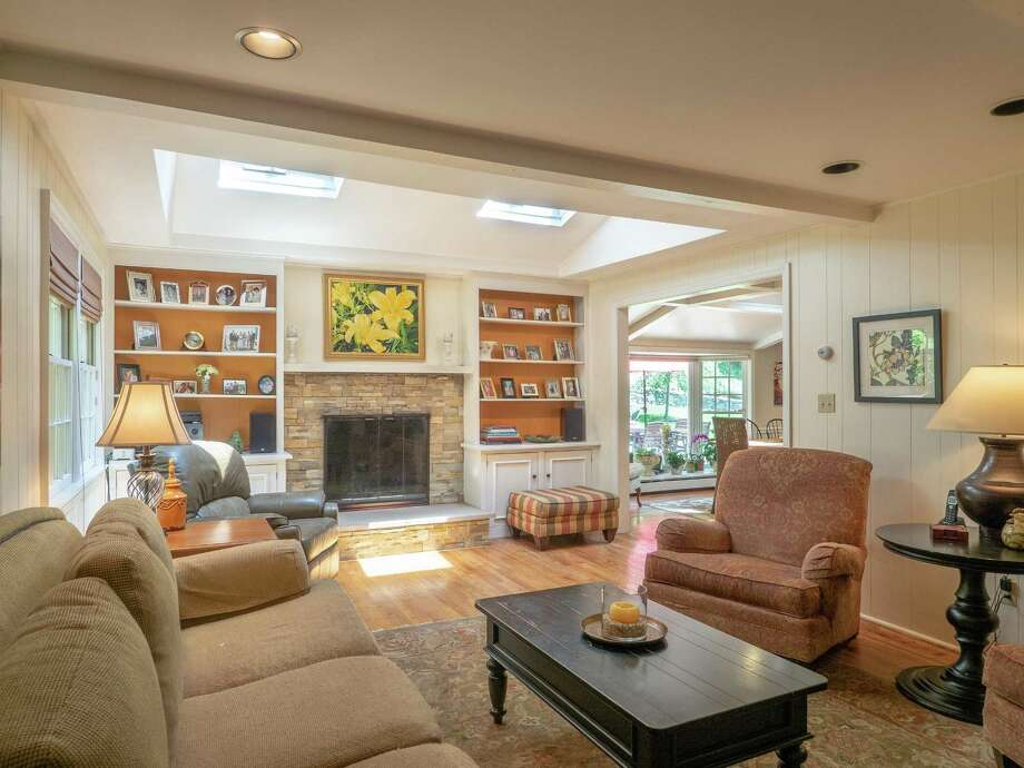 The family room at 63 Saddle Ridge Road feature built-ins that frame a stone fireplace and skylights. This custom-built colonial is in a South Wilton cul-de-sac. Photo: Budd Properties, William Raveis Real Estate / ONLINE_CHECK