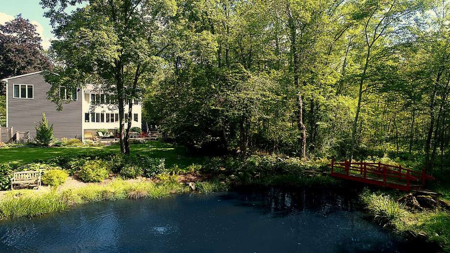 The Brookfield contemporary at 24 Merwin Brook in Brookfield features a backyard pond and an original designed bridge spanning the stream that flows into the pond. Photo: Berkshire Hathaway HomeServices New England Properties / ONLINE_CHECK