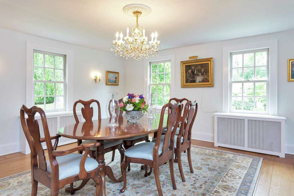 The formal dining at 21 Buttonwood Lane in Darien has southern and eastern windows, wainscoting and a chandelier.