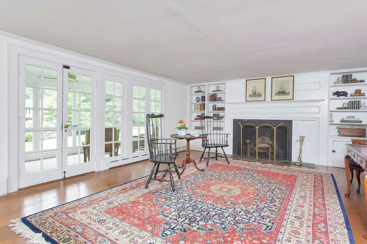 The living room at 21 Buttonwood Lane in Darien has paneling around a marble fireplace with built-ins and French doors to a screened-in porch.
