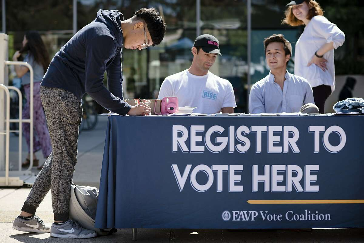 Cal student Harry Lee, left, registers to vote at the VoteCrew table during National Voter Registration Day on the UC Berkeley campus in Berkeley, Calif., on Tuesday September 25, 2018