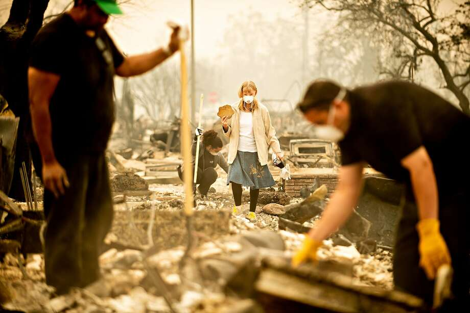 Astrid Granger recovers an item from her Coffey Park home after the fire. Photo: Noah Berger / Special To The Chronicle 2017