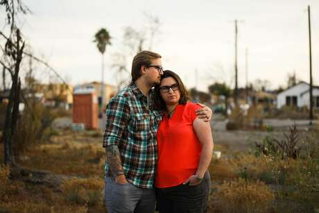 Cole Geissinger and his wife Melissa Geissinger embrace as they stand for a portrait at the site of their destroyed home after the Tubbs Fire tore through it last year in Santa Rosa, California, on Thursday, Sept. 27, 2018.