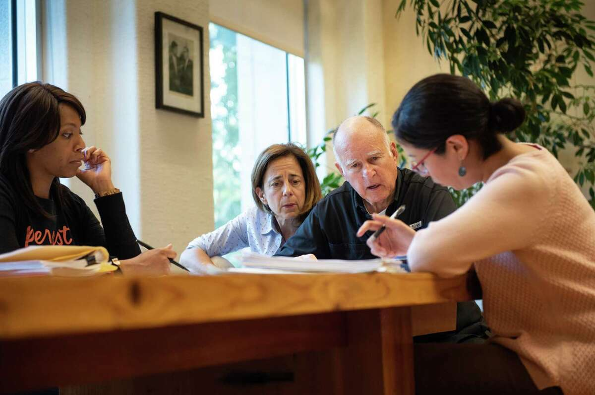 Governor Jerry Brown reviews legislation in his office with staff on his final day of bill action as governor, at the state Capitol in Sacramento on September 30. With the governor, from left, are Legislative Secretary Camille Wagner, first lady Anne Gust Brown and Deputy Legislative Secretary Graciela Castillo-Krings.