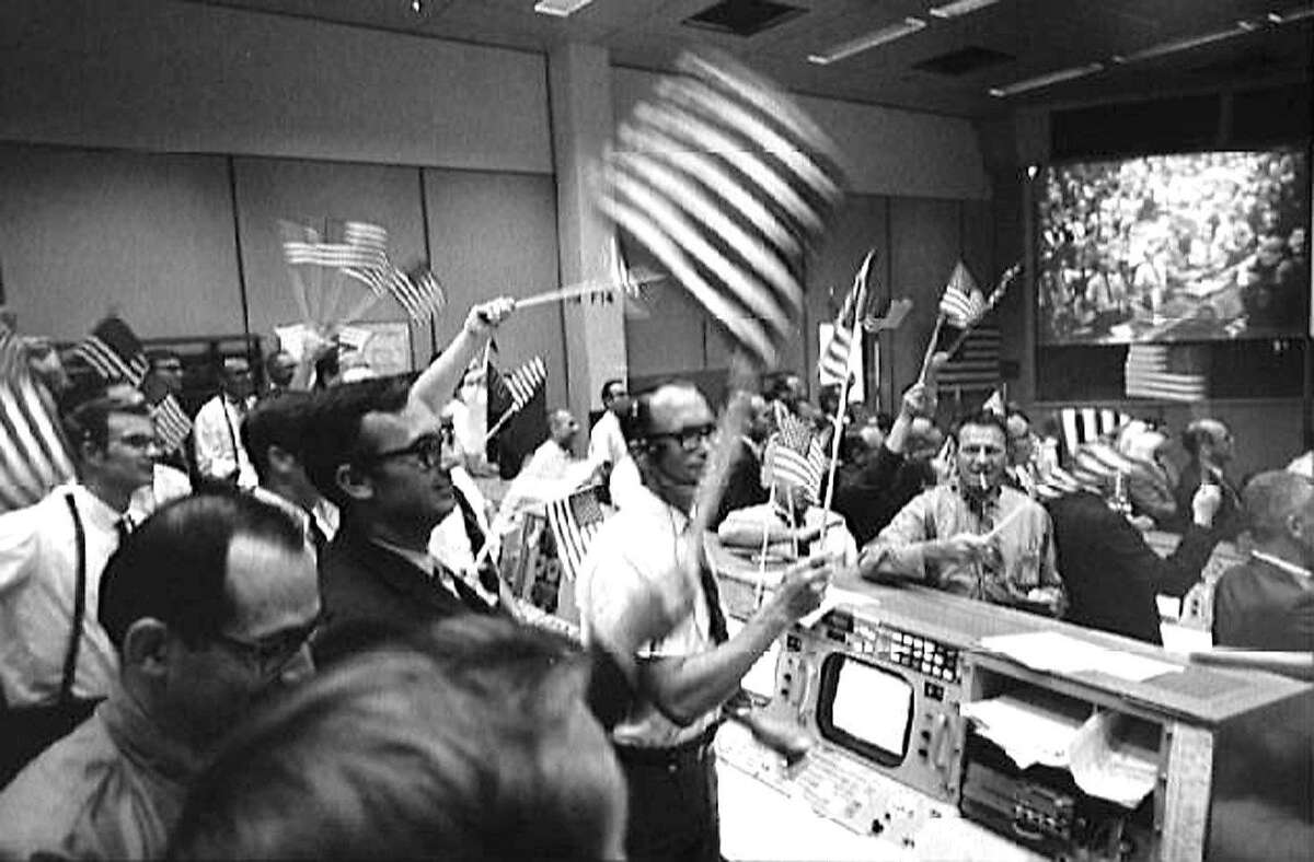 FILE-- Mission control personnel wave flags to celebrate the the return to earth of Apollo 11 on July 24, 1969.