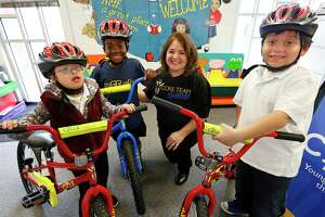 Houston Hero Debbie Taggart, center, helped first graders Milly Hernandez, Paris Daniels and Andres Carcamo get bikes at the Neff Early Learning Center
