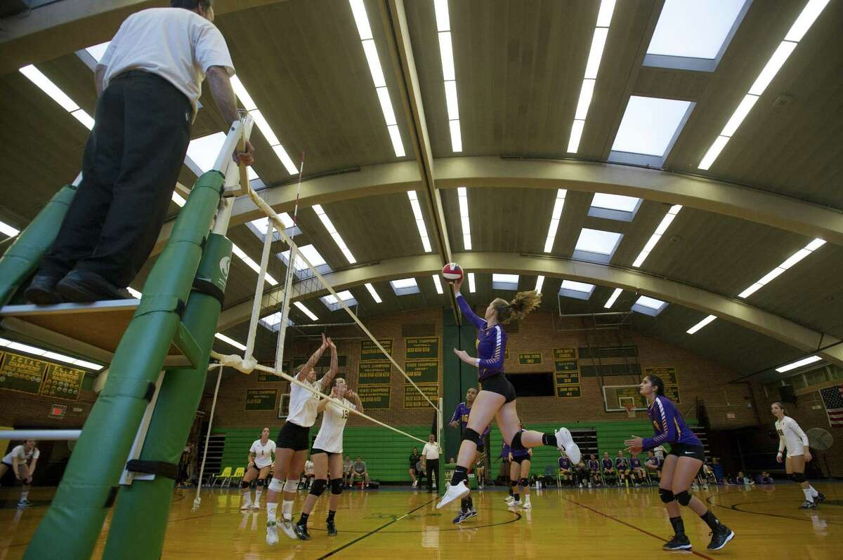 Westhill High School senior Nikki Newcomer leaps and hits the ball over the net during a varsity girls volleyball game against Trinity Catholic High School inside Trinity Catholic's Walsh Court in Stamford, Conn. on Monday, Oct. 1, 2018.