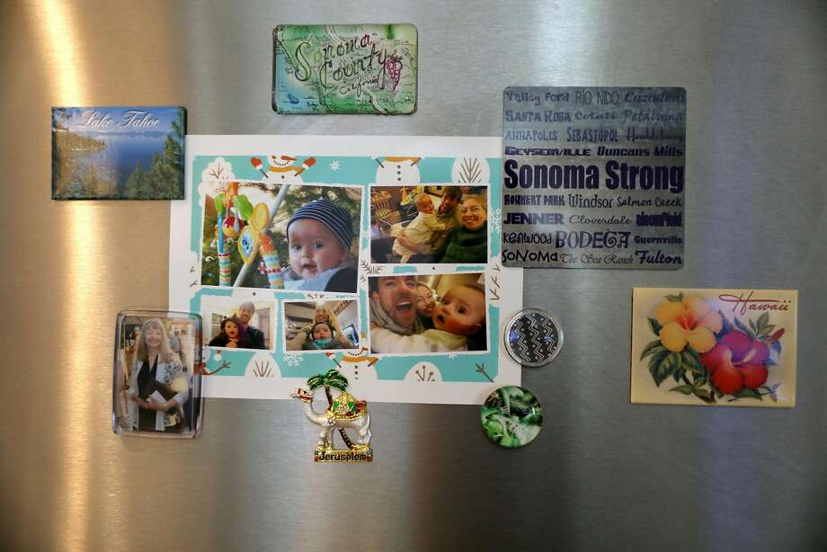 Astrid and Henry Granger decorated their fridge in a Santa Rosa rental with personal photos after the Tubbs Fire consumed their home.  Photo: Guy Wathen / The Chronicle