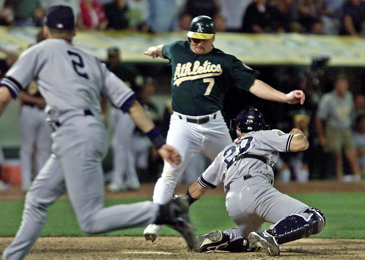 Oakland Athletics' Jeremy Giambi, center, is tagged out at home by New York Yankees' Jorge Posada, right, during Game 3 of the American League Division Series, in Oakland, Calif., Saturday, Oct. 13, 2001. Giambi tried to score from first on a double from Terrence Long in the seventh inning. At left is Yankees short stop Derek Jeter who assisted with a throw from between first and home. (AP Photo/Eric Risberg)