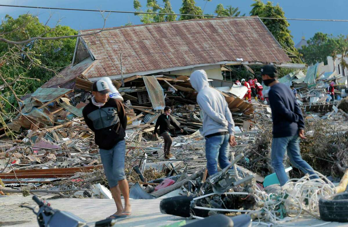 People survey the damage to a residential area following a massive earthquake and tsunami at Talise beach in Palu, Central Sulawesi, Indonesia, Monday, Oct. 1, 2018. A mass burial of earthquake and tsunami victims was being prepared in a hard-hit city Monday as the need for heavy equipment to dig for survivors of the disaster that struck a central Indonesian island three days ago grows desperate. (AP Photo/Tatan Syuflana)