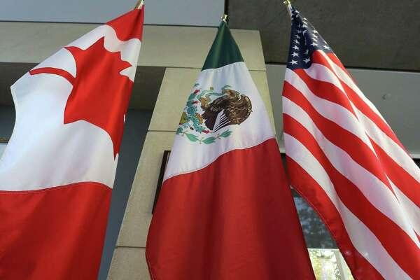 (FILES) Esta fotografía tomada el 24 de septiembre de 2017, muestra las banderas canadiense, mexicana y estadounidense en el lobby donde se llevó a cabo la tercer ronda de negociaciones en Ottawa, Ontario. Los tres países han eliminado los aranceles mutuos a diferentes productos que mantuvieron por varios meses.