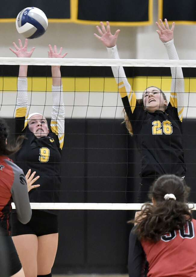 Amity's Zoe DiZenzo, left, and teammate Caroline Fertman try to block a shot by Cheshire on Monday. Photo: Peter Hvizdak / Hearst Connecticut Media / New Haven Register