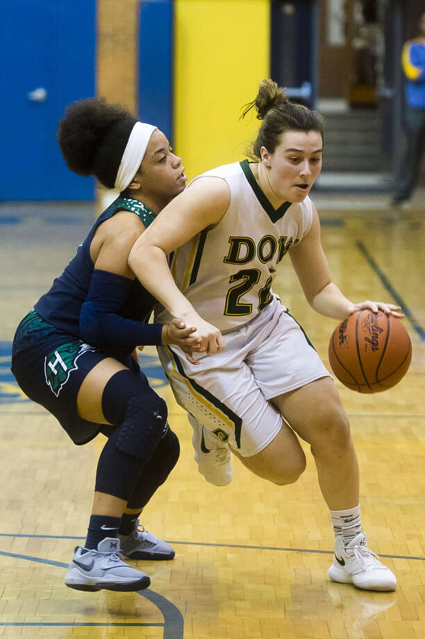 Dow High's Maizie Taylor drives past Saginaw Heritage's Lolo Reed during a district tournament game in March 2018. Photo: Daily News File Photo