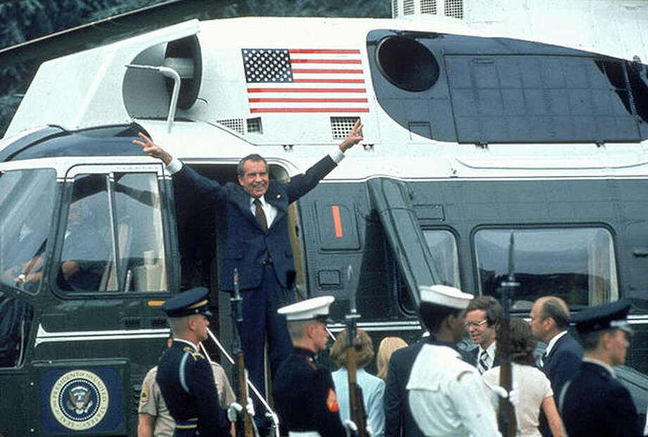 "President Richard Nixon with arms outstretched with ""v""d fingers at doorway to helicopter as he departs after his resignation. Bill Pierce 