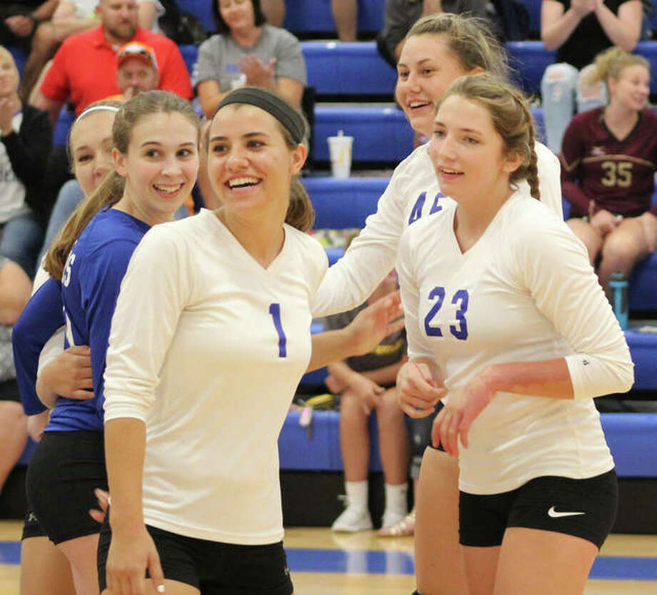 Brussels' Toni Odelehr (1) and Holly Kinder (23) celebrate a set victory over CM with teammates Samantha Macauley (dark jersey) and Logan Jacobs (back right) in a win at the Roxana Tourney in the Raiders' season opener on Aug. 21. The Raiders were at home Monday night and swept Pleasant Hill in two sets. Photo: Greg Shashack / The Telegraph