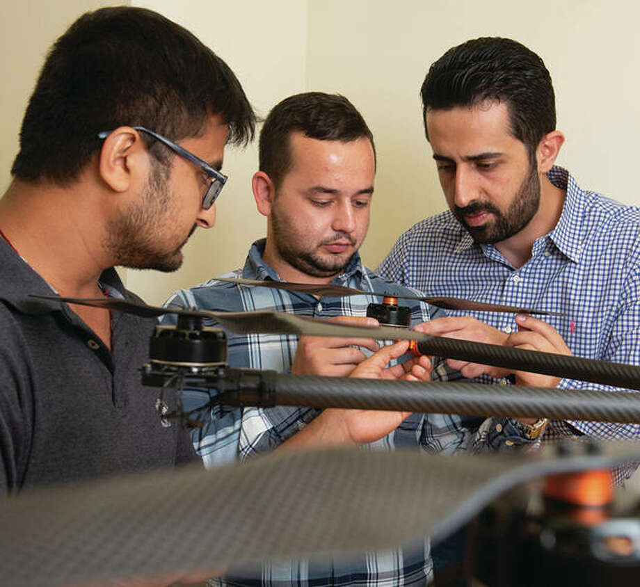 SIUE School of Engineering's Nima Lotfi, PhD, (back) and his students Nedret Ramic (middle), a mechanical engineering graduate student, and Pratik Lamsal, a senior mechanical engineering major, assemble a large drone. Photo: SIUE Photo