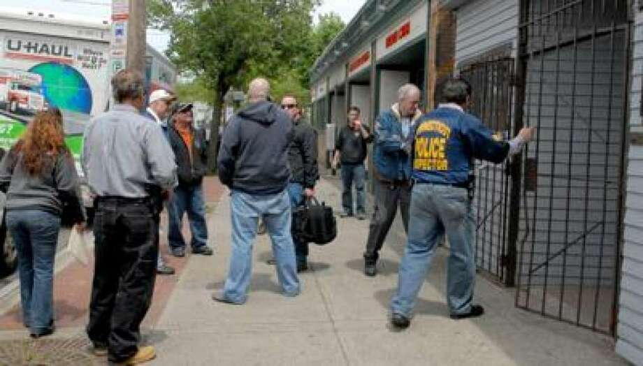 Law enforcement personnel, including state and city police and inspectors from the chief state's attorney's office, remove items from Ace Amusement & Cigarette Co. on Kimberly Avenue in New Haven in 2010. Photo: Peter Hvizdak/New Haven Register