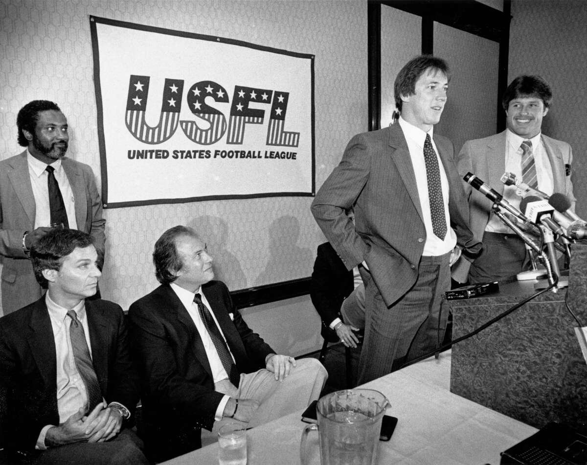 06/09/1983 - University of Miami teammates, quarterback Jim Kelly (at microphone) and running back Mark Rush (far right) speak to the news media following the announcement of their signing with the United States Football League (USFL) Houston Gamblers. (Standing at left) Gamblers GM Gene Burrough; (seated left to right) CEO Bernard Lerner and General partner/president Jerry Argovitz.