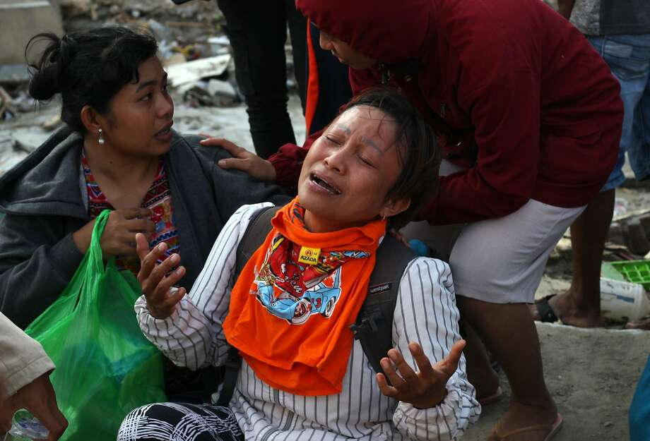 A woman grieves as she waits for a rescue teams to search for survivors at a collapsed building in Palu. Photo: Yusuf Wahil / AFP / Getty Images