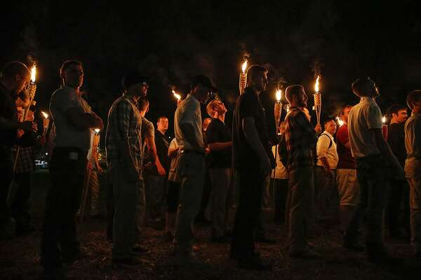 FILE - In this Aug. 11, 2017, file photo, multiple white nationalist groups march with torches through the University of Virginia campus in Charlottesville, Va. Multiple arrests have been made in connection with a white nationalist torch-lit march and rally in Charlottesville, Virginia, last year, federal authorities said Tuesday, Oct. 2, 2018. (Mykal McEldowney/The Indianapolis Star via AP, File)