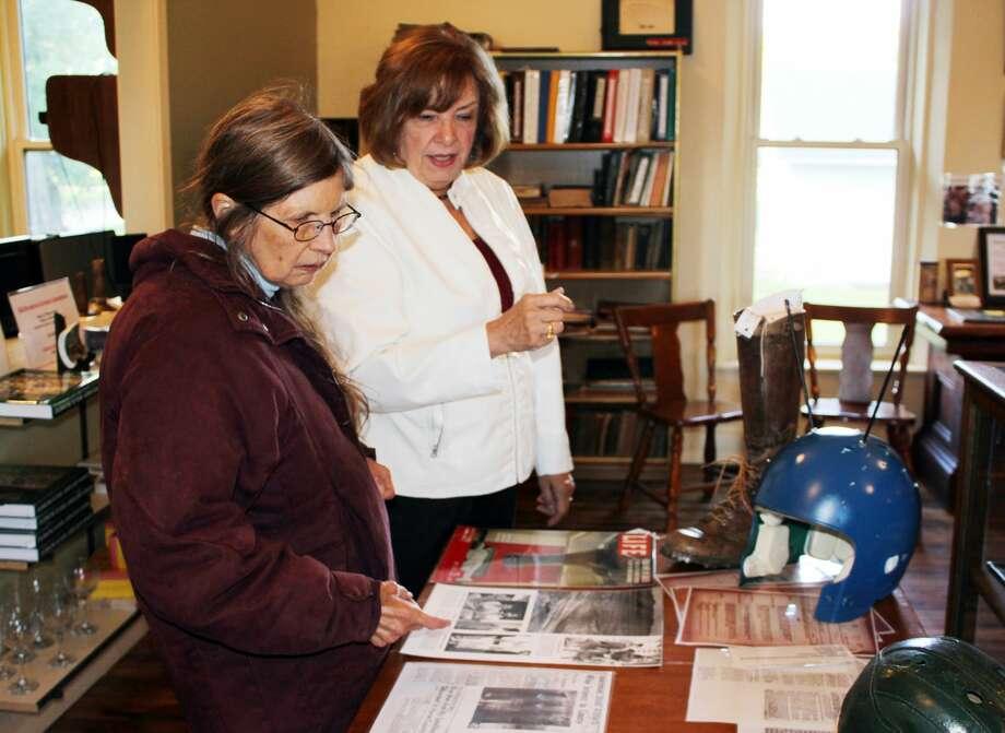 (Left) Sally Gilbert, of Fenton, studies the Blue Man exhibit at the Elkton Area Historical Society Museum, while Jayne White, member of the historical society, looks on. Photo: Brenda Battel/Huron Daily Tribune
