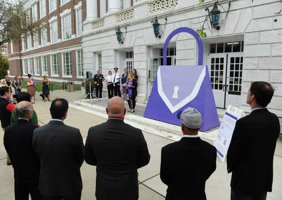 YWCA Greenwich Director of Domestic Abuse Services Meredith Gold speaks beside a large purple purse, the symbol of domestic abuse, during the Domestic Violence Awareness and Prevention Month Kickoff at Town Hall in Greenwich, Conn. Tuesday, Oct. 2, 2018. Representatives from the YWCA's domestic abuse services and Chief of Police James Heavey spoke about the prevelance of domestic violence and the importance of outreach services for victims. First Selectman Peter Tesei also read a proclamation to commemorate the start of Domestic Violence Awareness and Prevention Month. Events continue throughout the month including a candlelight vigil, art show reception, movie night and shopping event. Photo: Tyler Sizemore / Hearst Connecticut Media / Greenwich Time