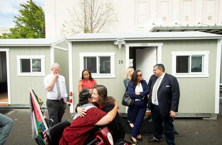 Oakland Mayor Libby Schaaf hugs a supporter, who gave her name as Na, while visiting Tuff Shed shelters adjacent to the Kaiser Convention Center in Oakland, Calif., on Tuesday, Oct. 2, 2018. The city plans to house up to 40 homeless people in the shelters as part of it's third Community Cabin site.