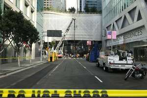 Workers at the Transbay Transit Center unload hydraulic jacks that will be used to temporarily support the damaged building while cracked beams are inspected.