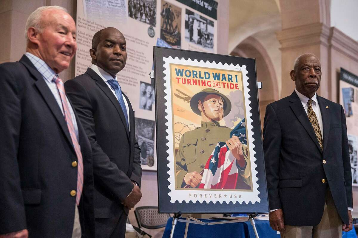 (From left) Marine Corp Major General Mike Myatt, San Francisco Postmaster General Abraham Cooper and San Francisco Fleet Week Board of Directors member Ed Flowers pose next to a large replica of a collectible stamp commemorating the centennial of World War I during an unveiling ceremony at the War Memorial Veterans Building in San Francisco, Calif. Tuesday, Oct. 2, 2018.