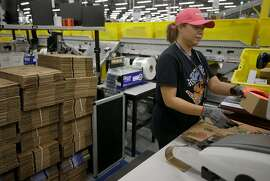 Stacey Morales packes customer's orders at the Amazon HOU2 Fulfillment Center, 10550 Ella Blvd., Thursday, Sept. 6, 2018, in Houston.